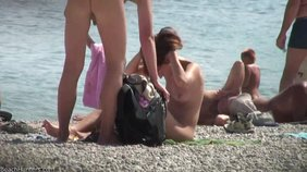 Long-haired amateur girlfriend showing her tanned tits on a nudist beach