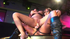 Two perverted chicks and a strapon are making out on a stage