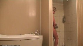 Chubby blonde milf is seductively rubbing her hairy pussy under the shower