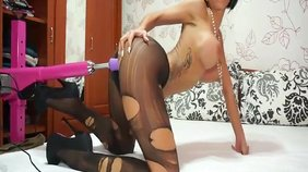 Pantyhose-clad brunette whore takes a big fake dick from behind on camera